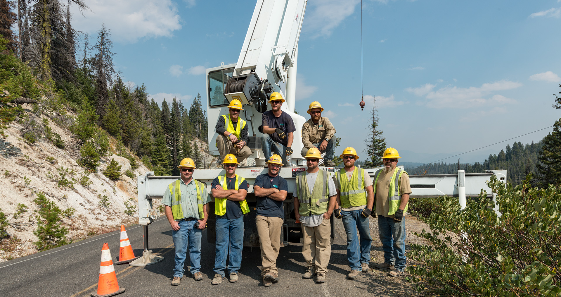 Idaho Power employees standing in front of a crane