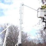 tree_trimmers_in_bucket_trucks_working_to_trim_trees