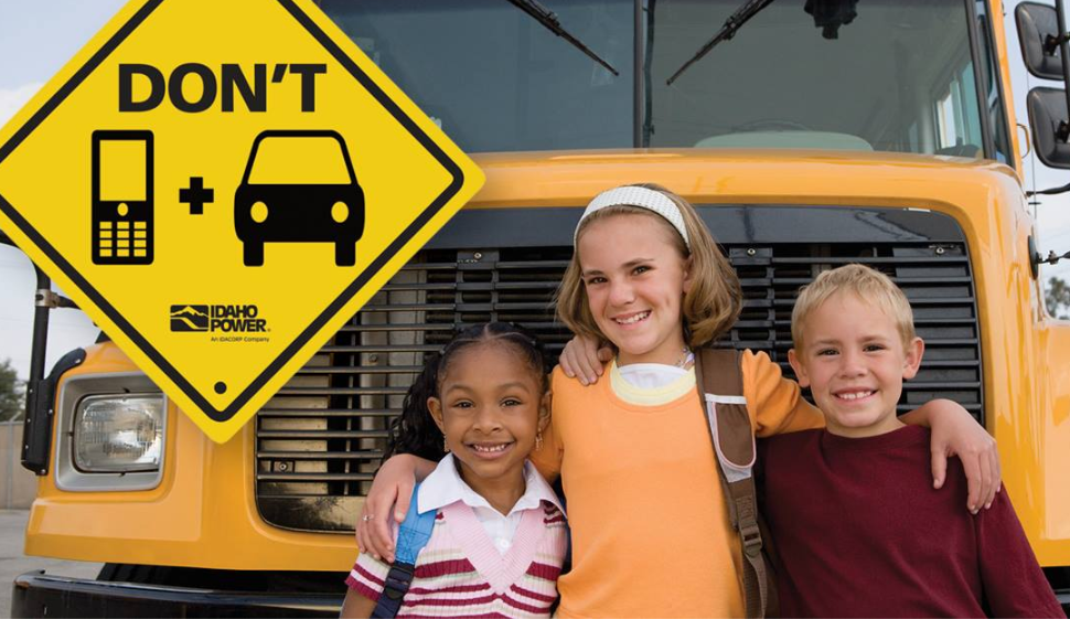 Image of kids by a bus and a sign to just drive.