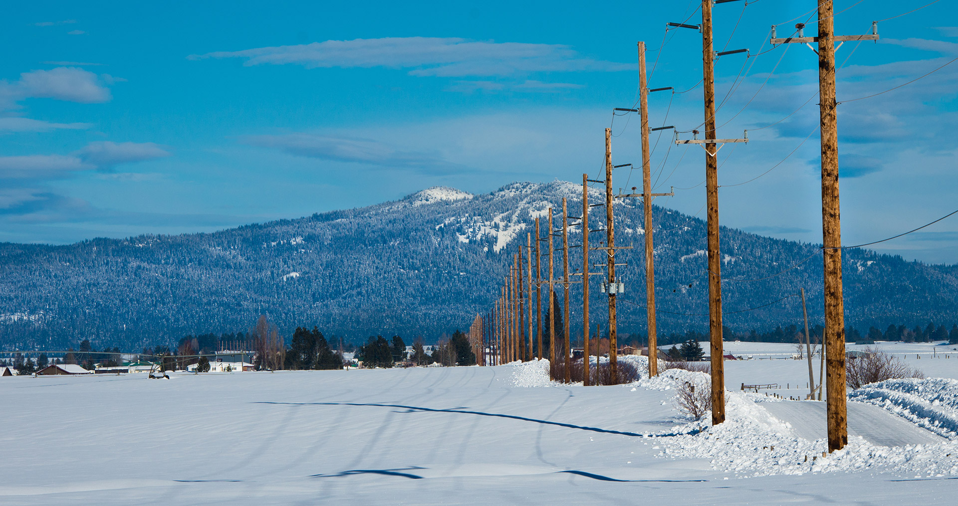 Winter scene of snow, power lines, and mountains.