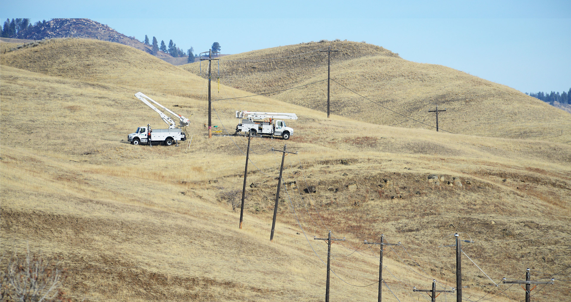 Image of trucks by power poles in the foothills