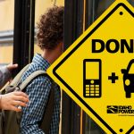 Kids getting on a school bus with a sign that says don't text and drive